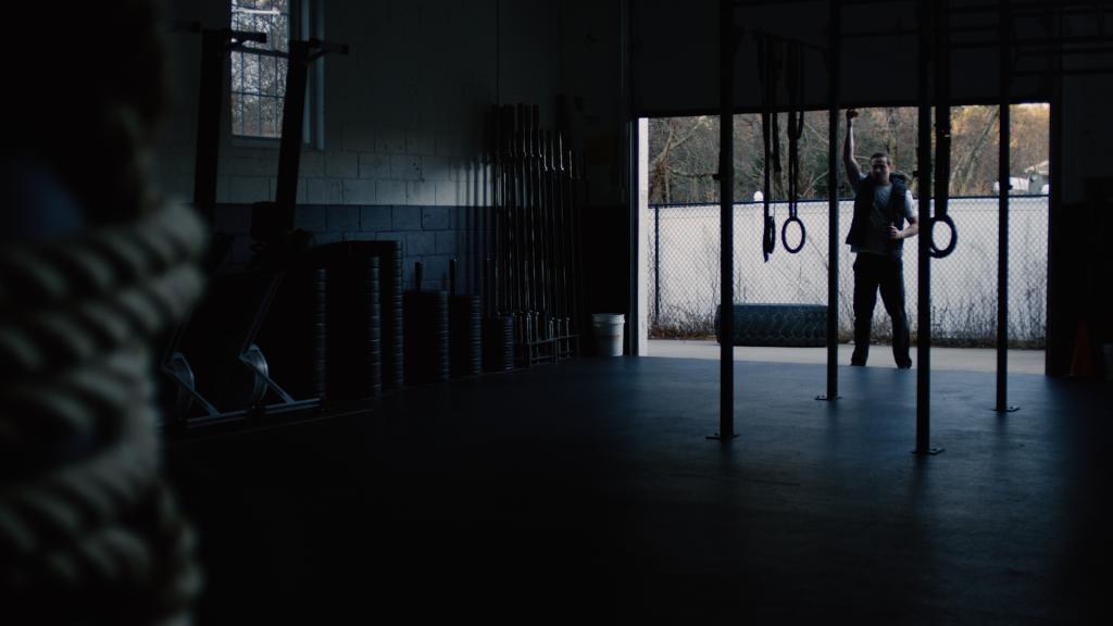 Man opening the door to his gym.