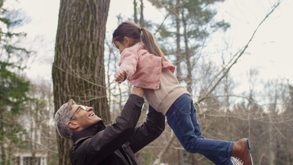 Grandfather holder granddaughter over his head.